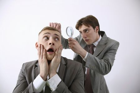 Man examining his friends hair with magnifying glass photo