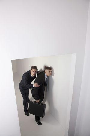 eavesdropping: Men eavesdropping, head resting against wall Stock Photo