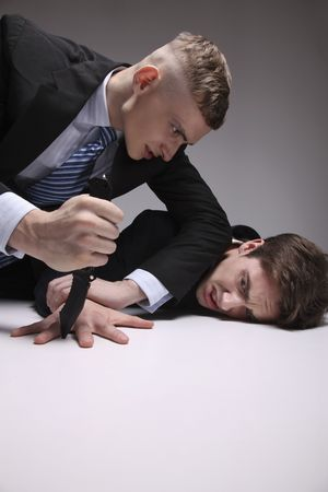 office politics: Man threatening to cut another mans finger with a knife