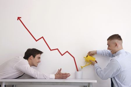 Man watering pot of line graph encouraging business growth, another man watching photo