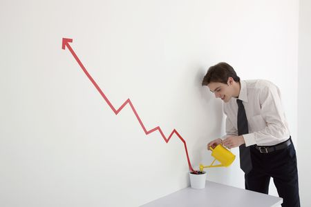 watering can: Man watering pot of line graph encouraging business growth Stock Photo
