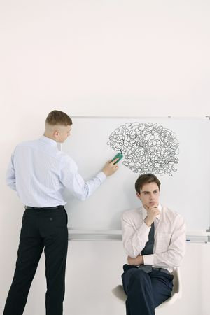 Man erasing scribbles drawn above another mans head photo
