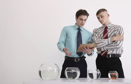 Two men evaluating various sizes of fishbowls photo