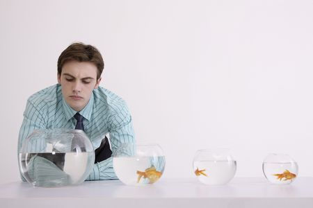 Man looking at empty fish bowl, contemplating photo