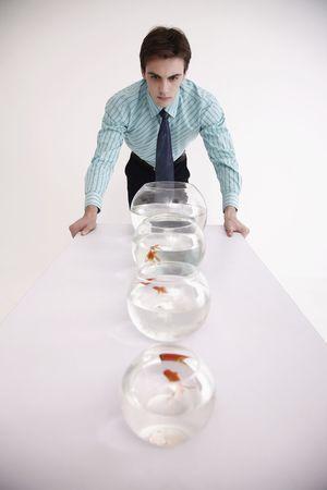 Man looking at row of fish bowls Stock Photo - 6546349
