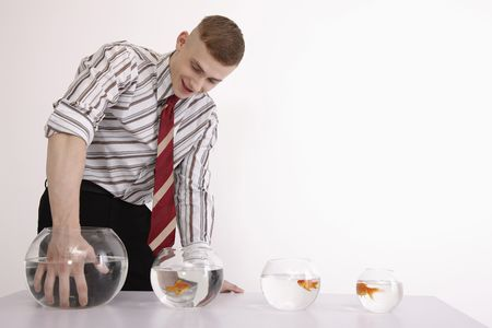 Man with hand in biggest fish bowl smiling Stock Photo - 6546370