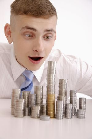 Man looking excited over stacks of coins photo