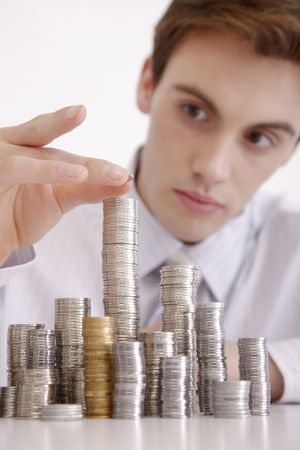 french ethnicity: Man carefully stacking coins Stock Photo