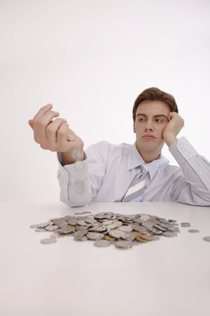 french ethnicity: Man looking bored with coins dropping from his hand Stock Photo
