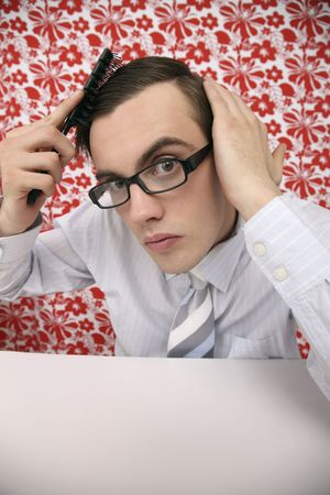 Man with glasses combing his hair photo