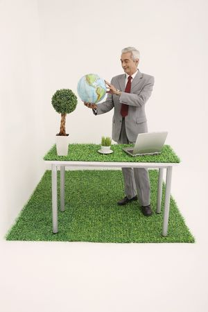 Businessman standing at his table holding globe photo