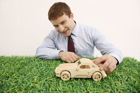 bulgarian ethnicity: Businessman playing with wooden toy car Stock Photo
