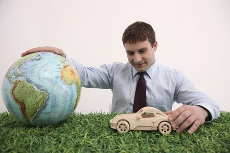 Businessman playing with wooden toy car and globe photo