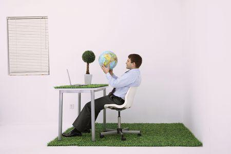 Businessman looking at globe photo