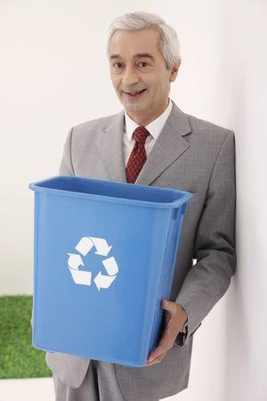 papelera de reciclaje: Empresario sosteniendo una papelera de reciclaje