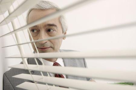southern european descent: Businessman peering through window blinds