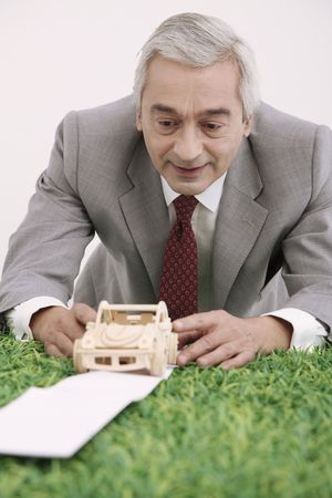 italian car: Businessman playing with wooden toy car Stock Photo