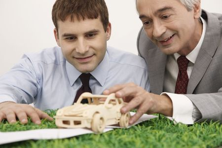 Businessmen playing with wooden toy car Stock Photo - 6581069