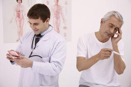 contando dinero: Doctor de recuento de dinero, paciente de celebrar el term�metro con la mano sobre la cabeza Foto de archivo