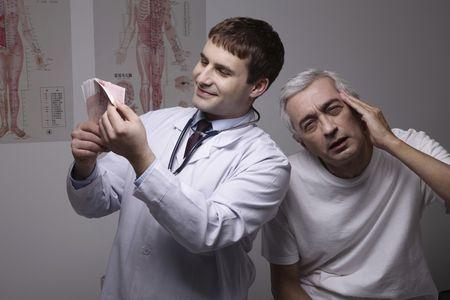 bulgarian ethnicity: Doctor counting money, patient having headache Stock Photo