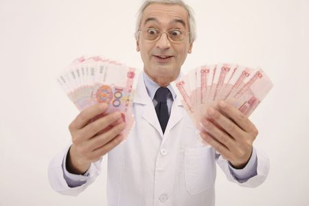 doctor holding money: Doctor looking happily at the money he is holding