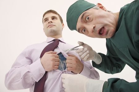 bulgarian ethnicity: Surgeon fixing circuit board on businessmans body Stock Photo