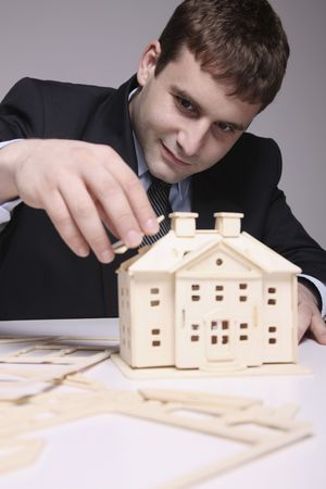 Man building a wooden house model photo