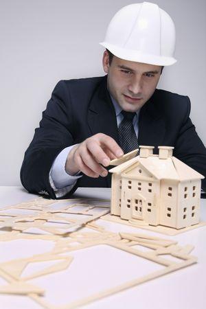 southeastern european descent: Man building a wooden house model