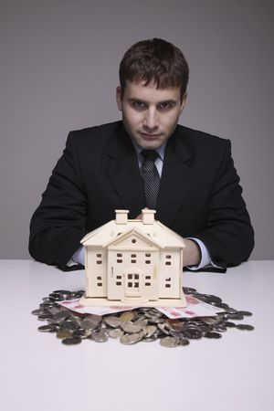 bulgarian ethnicity: Businessman with wooden house model and money on the table Stock Photo