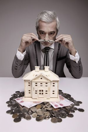 Businessman taking a clearer view of the wooden house model from his spectacles photo