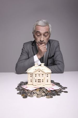 Businessman touching his chin while looking at wooden house model photo