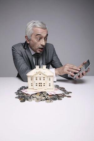 Shocked businessman using calculator photo