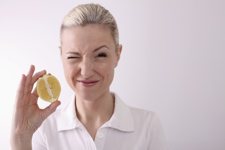 squinting: Woman squinting while holding halved lemon
