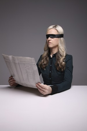 Blindfolded businesswoman reading newspaper Stock Photo - 6974368