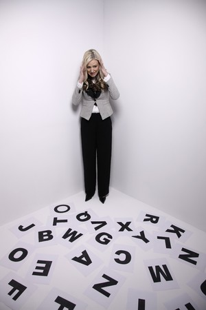 Businesswoman standing in corner, looking at alphabets on the floor photo