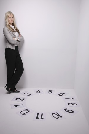 Businesswoman smiling while standing next to a circle of numbers photo
