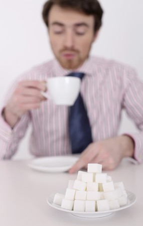 Man enjoying a cup of coffee, focus on sugar cubes Stock Photo - 6866682