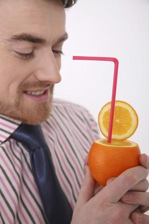 north western european descent: Man holding orange with drinking straw  Stock Photo