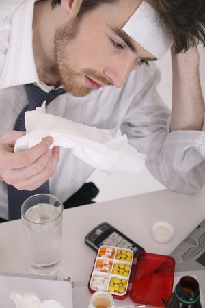 Man having flu and fever holding tissue photo