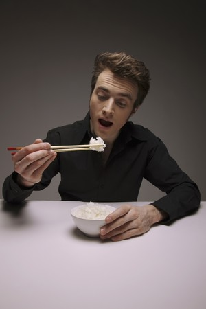 Man eating white rice with chopsticks Stock Photo - 6990622