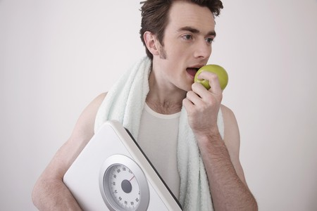 Man holding scale and eating a green apple Stock Photo - 6990623