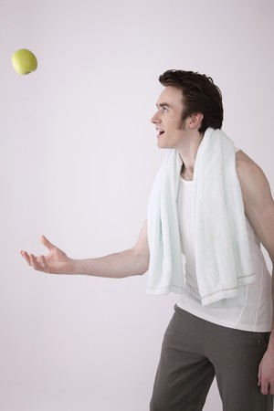 Man throwing green apple up in the air Stock Photo - 6990624