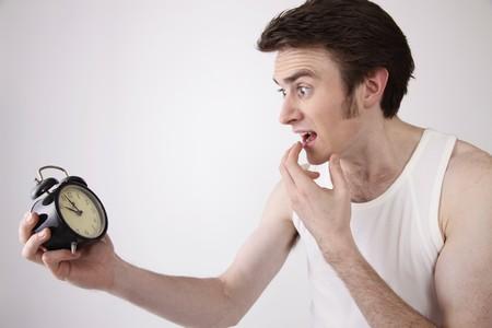 north western european descent: Man looking at alarm clock Stock Photo