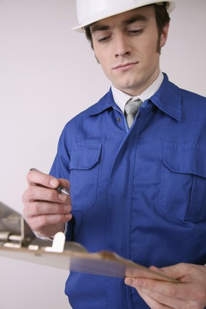 north western european descent: Man writing on clipboard Stock Photo