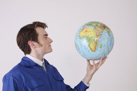 north western european descent: Man holding globe smiling Stock Photo