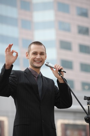 Businessman showing OK sign while giving speech photo