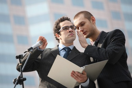 Man whispering into businessman's ear, businessman covering the microphone while listening Stock Photo - 6990640