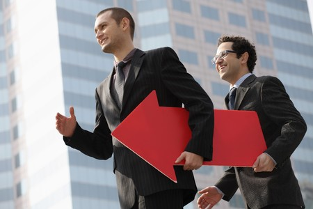 Businessmen walking with red arrow sign photo