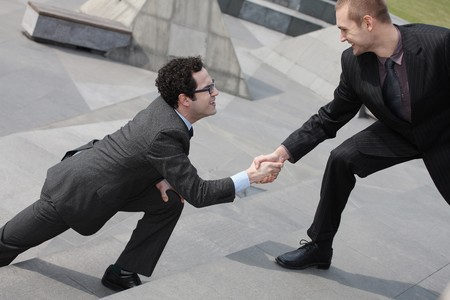 Businessman offering outstretched hand to another businessman Stock Photo - 6990643