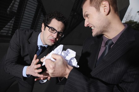 Businessman crumpling paper, another businessman looking sadly Stock Photo - 6990647